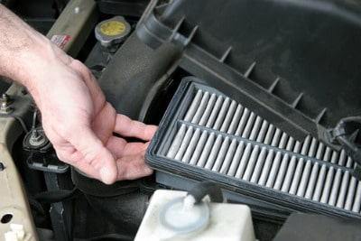 Man remove dirty air filter under car hood.