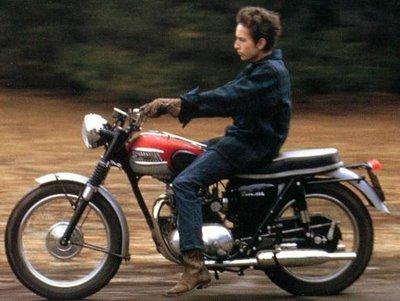 Bob Dylan riding on motorcycle.