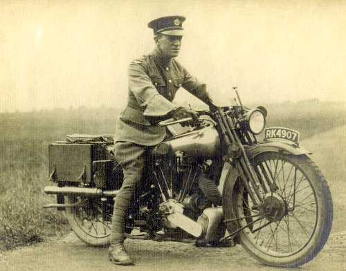 A military soldier wearing uniform riding on motorcycle.