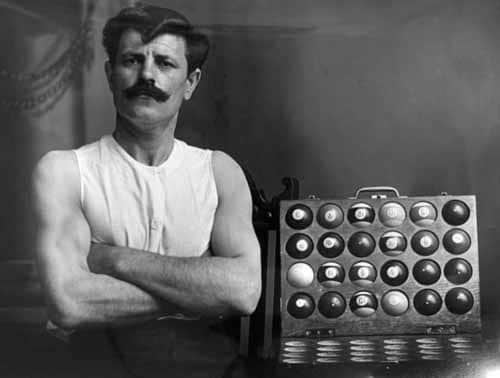 Man posing with billiards balls in sleeveless white shirt.