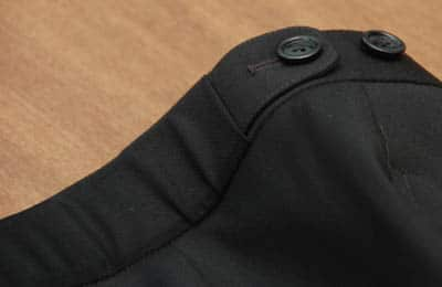Side tabs on a pair of black trousers.