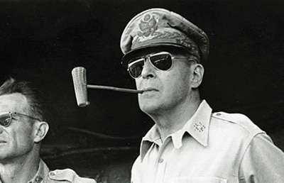 Douglas MacArthur smoking pipe while wearing sunglasses and hat.