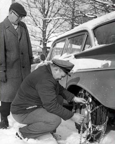 vintage man mechanic putting chains on car 1940s 1950s