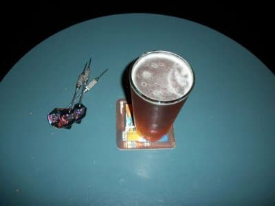 darts on table next to pint of beer