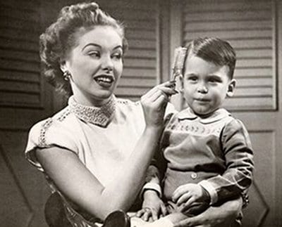 vintage little boy having hair brushed by mom