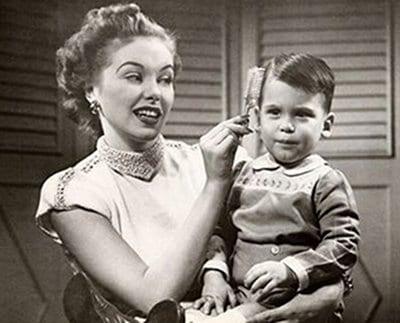 vintage little boy having hair brushed by mom