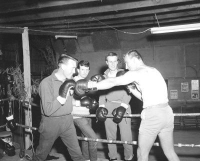 Two boxers having a bout in front of their friends in boxing ring.