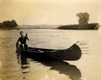 vintage man canoeing on lake alone solo