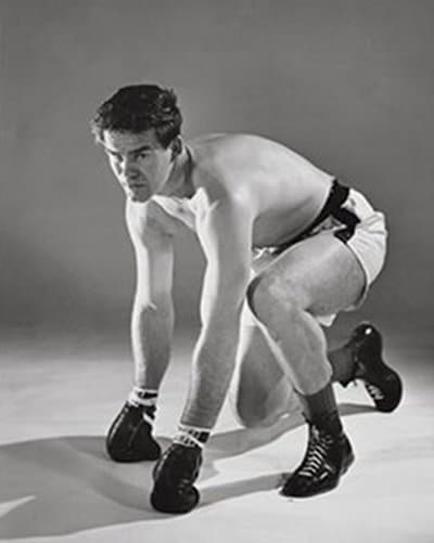 vintage boxer posing hands on ground gloves shorts