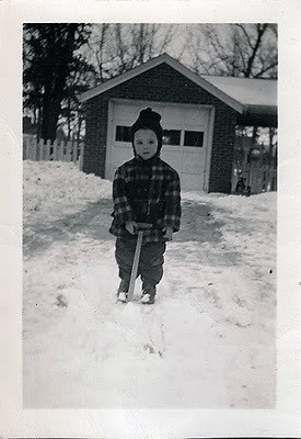 Vintage little boy shoveling snow from driveway.