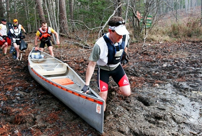 man hauling canoe swamp adventure race racing