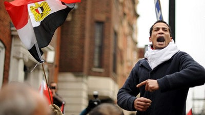 young man yelling Egyptian revolution flying flag