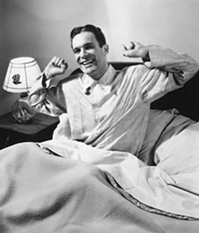 vintage man waking up in bed happy chipper