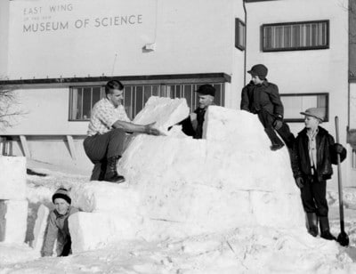 Vintage group of men making snow fort.