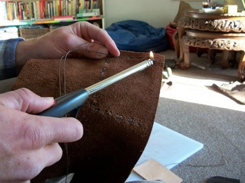 Burning the stitching wax for leather wallet.
