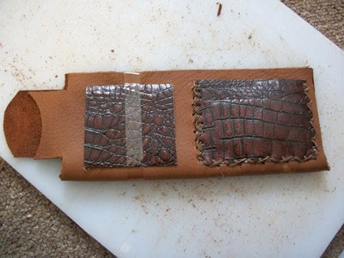 A leather wallet with cowhide pockets placed on white surface.