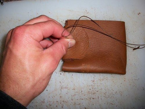 Man using threads for sewing the leather wallet.