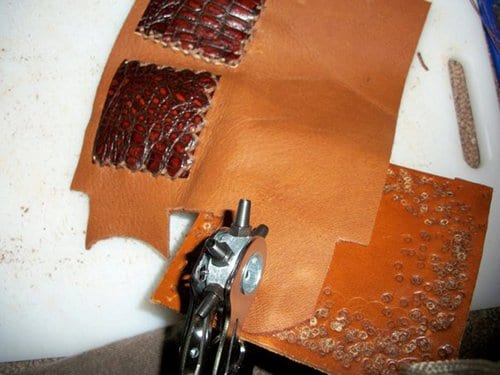 Using rotary punch to makes small holes on leather wallet.