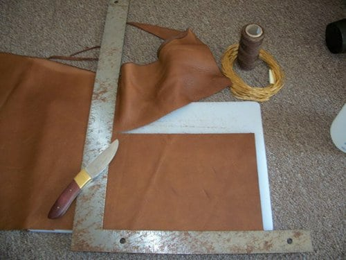 Cutting off the measured leather for leather wallet.