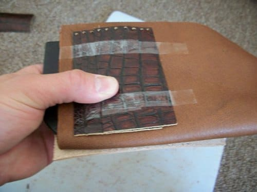 Man sticking the cowhide on leather wallet.