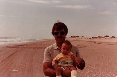 baby being held by dad on beach ocean
