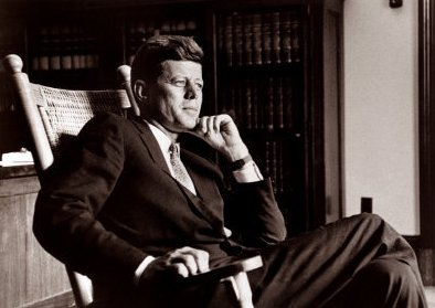 John Kennedy sit on a large rocking chair.