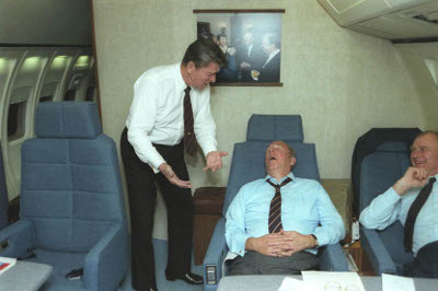 Ronald Reagan talking to sleeping man.