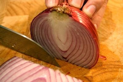 Man cutting onion with knife.