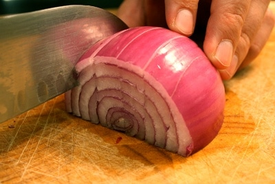 Man slicing onion with knife.