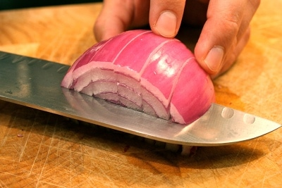 Man cutting onion with knife in horizontal view.
