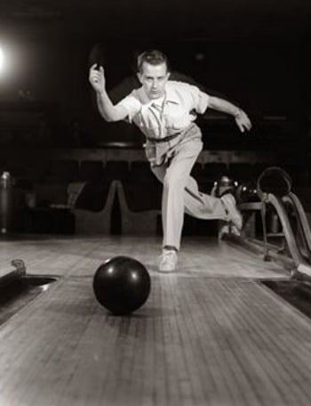 vintage bowler throwing bowling ball view from lane