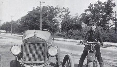 Charles Lindbergh sitting on motorcycle besides of car.