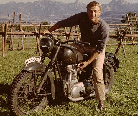 Steve Mcqueen riding on motorcycle in mountain area.