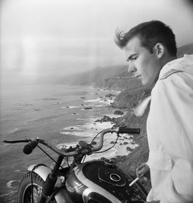 Thompson sitting on motorcycle and looking over the cliff.