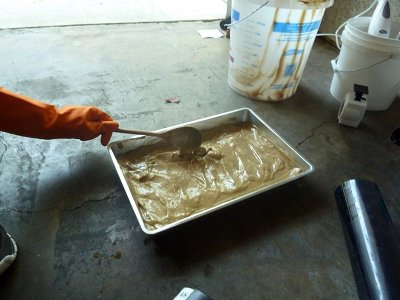 Man pouring molds into baking sheet for homemade soap bars.