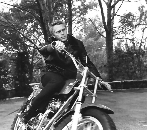 Steve Mcqueen riding on motorcycle.