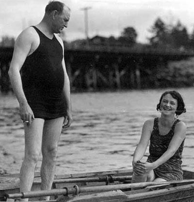vintage man standing in row boat bathing suit