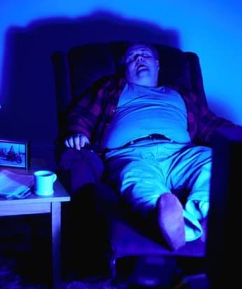 obese man sitting sleeping in chair tv blue light