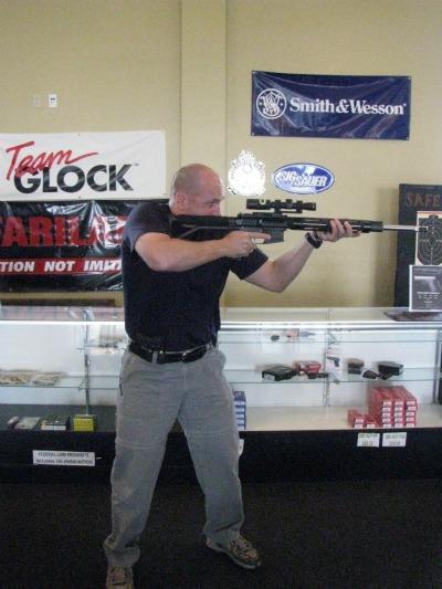 Man shooting a rifle in gun shop.