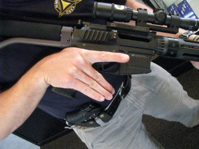 Man holding a rifle with pistol grip.