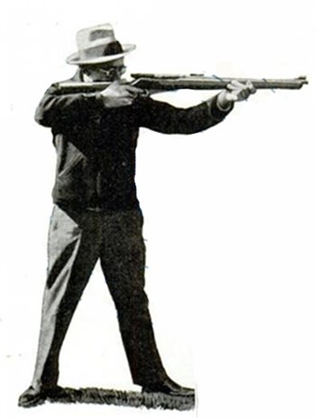 vintage man standing holding shooting rifle