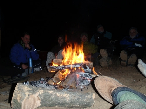 A group of man sitting around a fire.