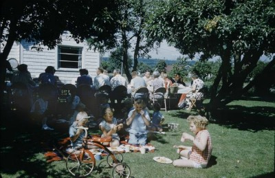 Vintage block party picnic outdoors and children eating together.