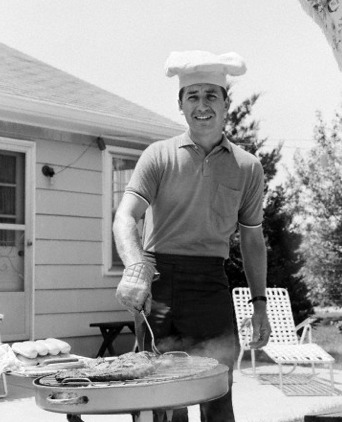 Vintage man wearing chef's hat grilling meat on patio.