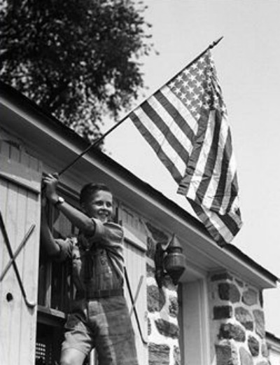 Vintage boy hanging american flag outside house window.
