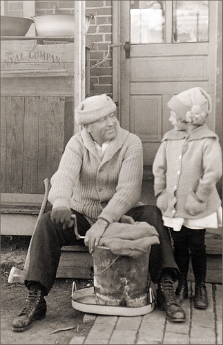 Vintage older man and child making homemade ice cream.