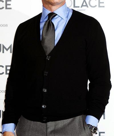 A man wearing cardigan sweater over dress shirt necktie.