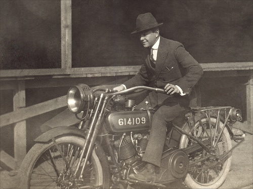 vintage man riding motorcycle 1920s 1930s wearing suit fedora