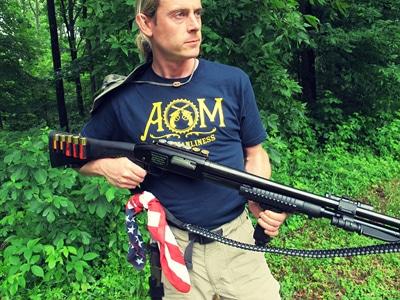 Man carrying shotgun and American bandana.