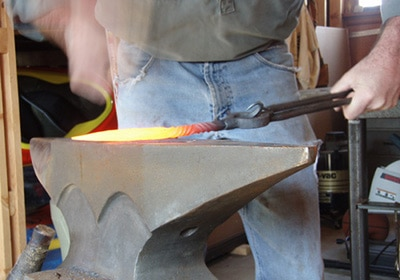 A man holding a hot iron and making cone on anvil edge.